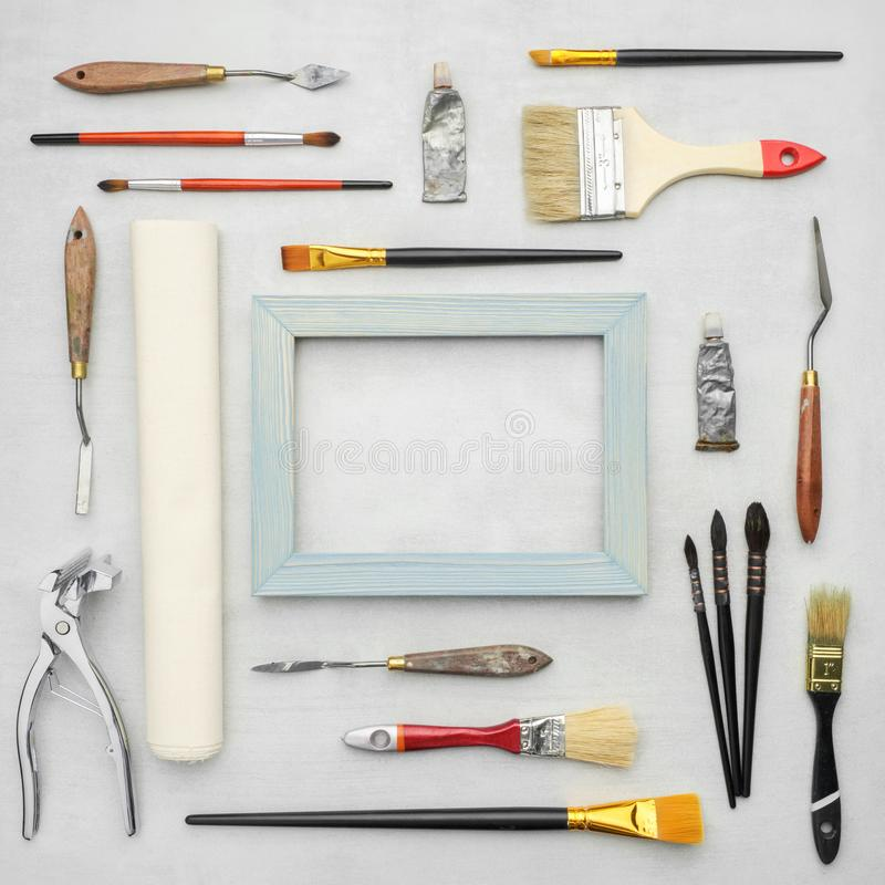 Paintbrushes, tubes of paints, palette knifes, artist canvas in roll, wooden frame, canvas stretcher pilers on marble background. royalty free stock images