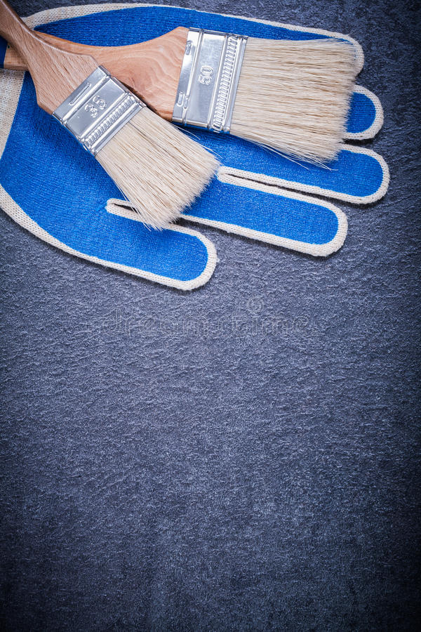Paintbrushes working gloves on black background. Construction concept stock photo