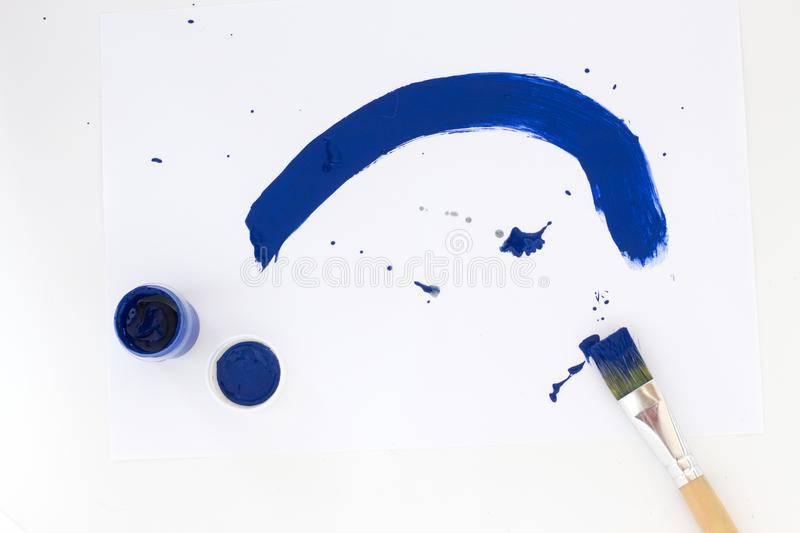 Painted abstract background blue stripe with paints and brushes on white paper background. stock images