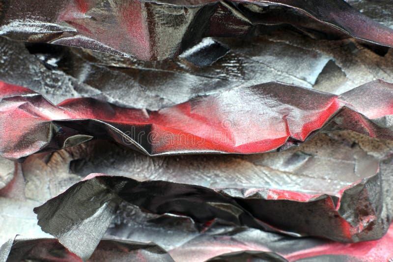 Painted amarrotou pedaços de papel na superfície de uma parede áspera Tons pretos vermelhos imagem de stock royalty free