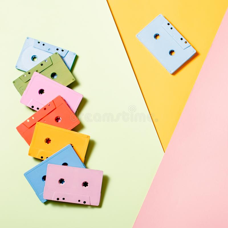 Painted audio cassettes on bright multicolor background, copy space, top view. Retro musical background stock image