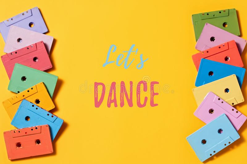 Painted audio cassettes on bright yellow background, let`s dance quote. Retro musical background royalty free stock images