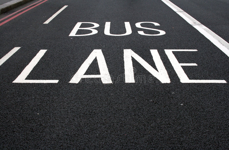 Painted bus lane sign on road. Bus lane sign painted on to tarmac road stock photo