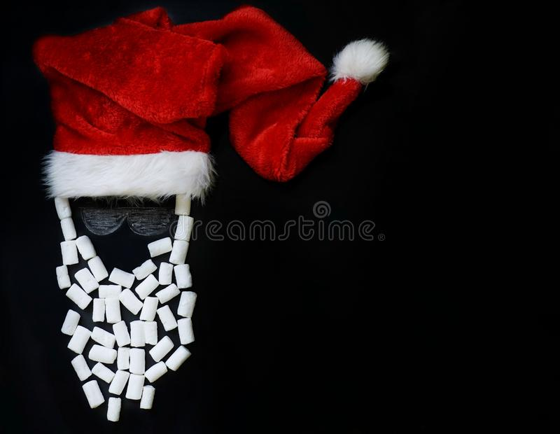 Painted with chalk Santa Claus with a real red cap and a beard of marshmallow on the slate, the concept of the new year and Christ. Mas stock photo