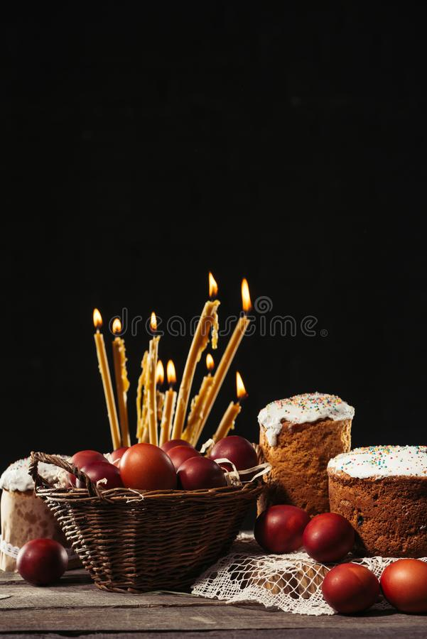 View of painted eggs in basket, willow twigs and delicious easter cakes. Painted chicken eggs in basket, burning candles and homemade easter cakes on black stock images