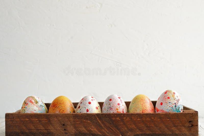 Painted a coloré des oeufs de pâques dans une boîte en bois foncée sur un fond clair photos libres de droits