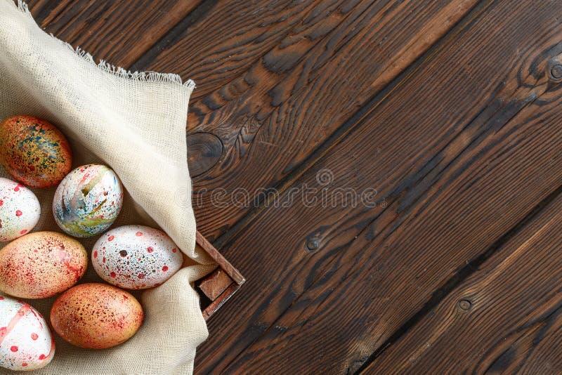 Painted coloreó los huevos de Pascua en lona en caja de madera oscura en fondo de madera imágenes de archivo libres de regalías