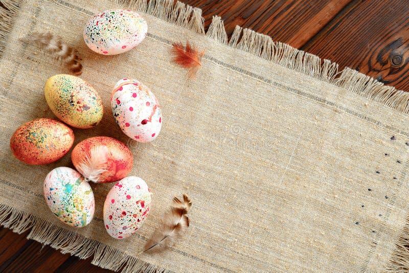 Painted coloreó los huevos de Pascua en lona en fondo de madera imagen de archivo