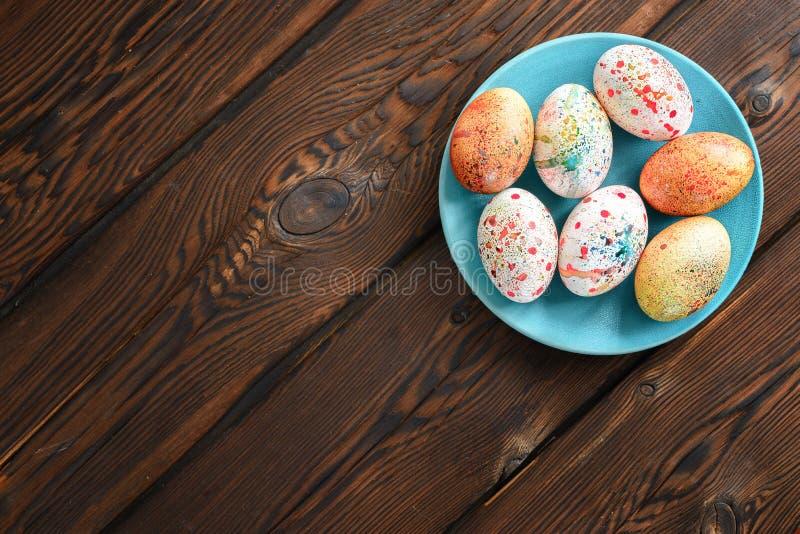 Painted coloreó los huevos de Pascua en una placa azul en un fondo de madera imagen de archivo