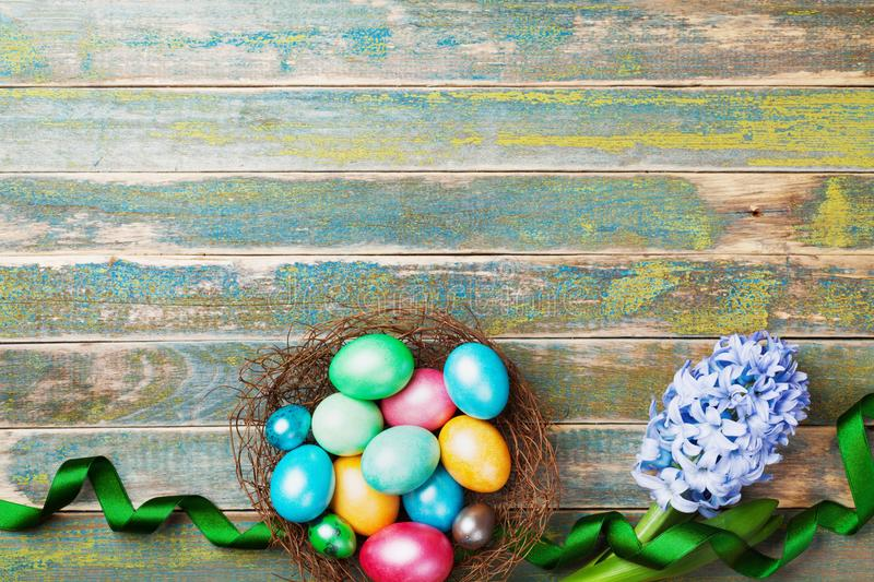 Painted colorful Easter eggs in nest with hyacinth flowers and ribbon top view. Festive background for spring holiday. royalty free stock photos