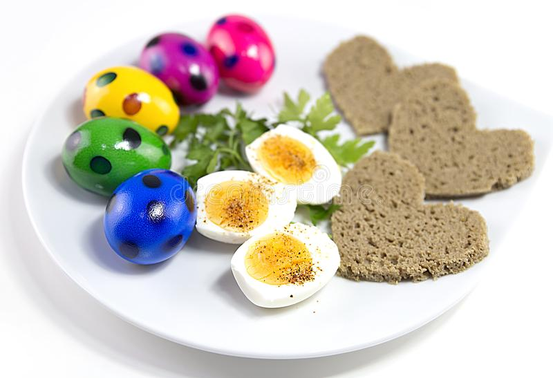 Easter eggs on a plate with bread and greens, registration of a dish for a holiday of Easter royalty free stock photo