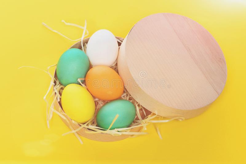 Painted easter colorful eggs in wooden box on yellow background royalty free stock image