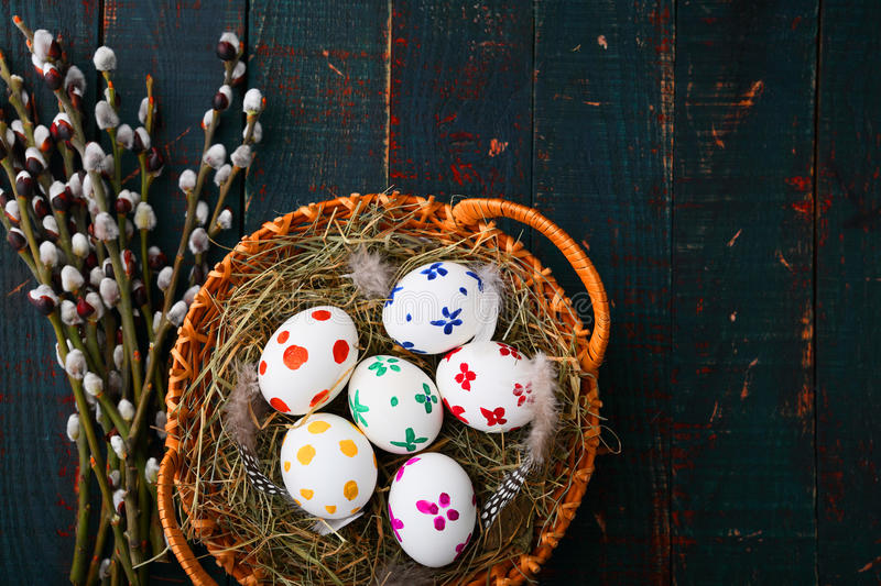 Painted Easter eggs in basket and willow branches on wooden table royalty free stock images
