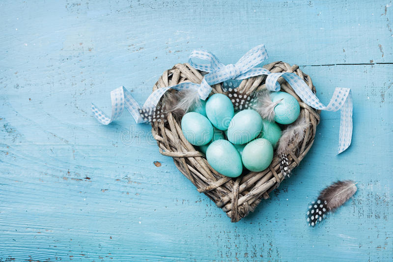 Painted Easter eggs in heart nest on vintage turquoise background top view in flat lay style. stock photography