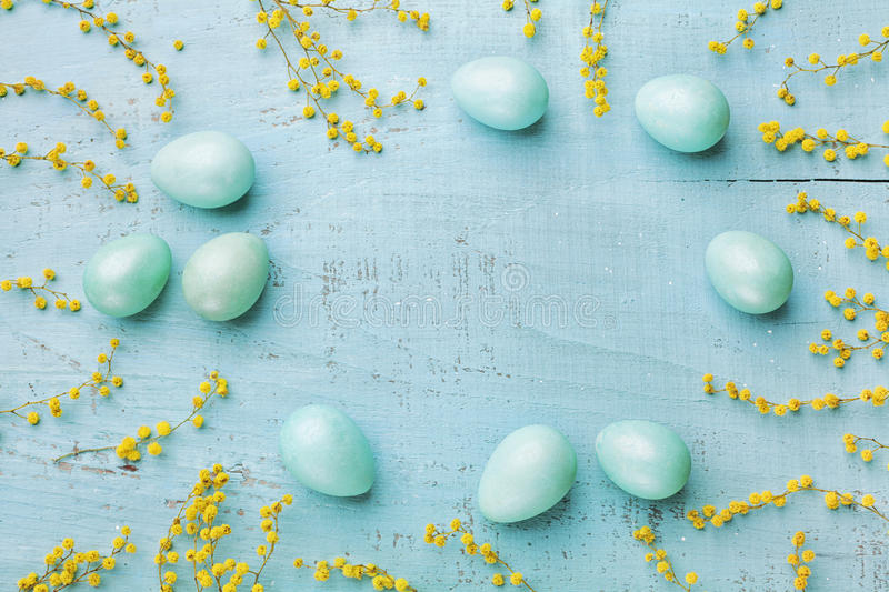 Painted Easter eggs and yellow mimosa flower on vintage wooden background top view in flat lay style. Clean space for text. Painted Easter eggs and mimosa stock photos