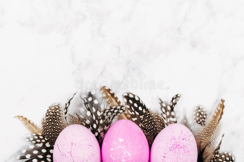 Painted Easter pink eggs with stylish feathers on a marble background. Holiday background. Flat lay, top view stock photo