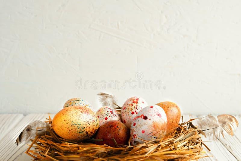 Painted färgade påskägg i ett rede av nytt hö på en träbakgrund royaltyfri foto
