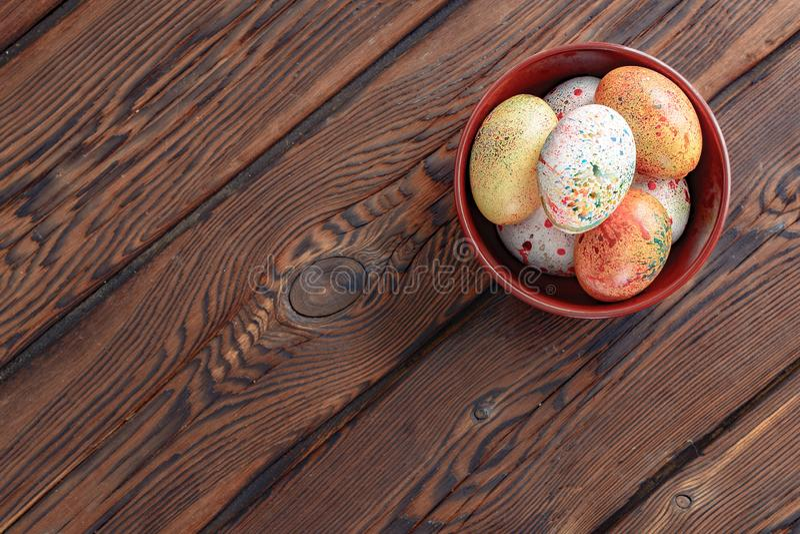 Painted färgade påskägg på en brun platta på en träbakgrund royaltyfri bild