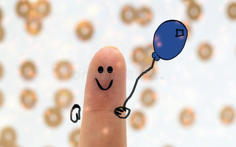 Painted finger smiley with balloon, birthday concept, happy fun creation background. Closeup stock image