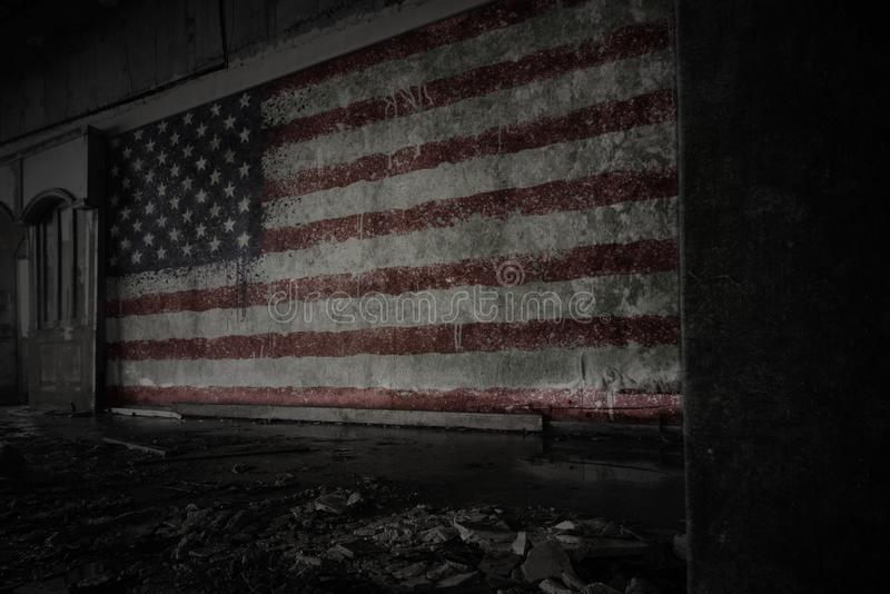 Painted flag of united states of america on the dirty old wall in an abandoned ruined house. Concept stock image