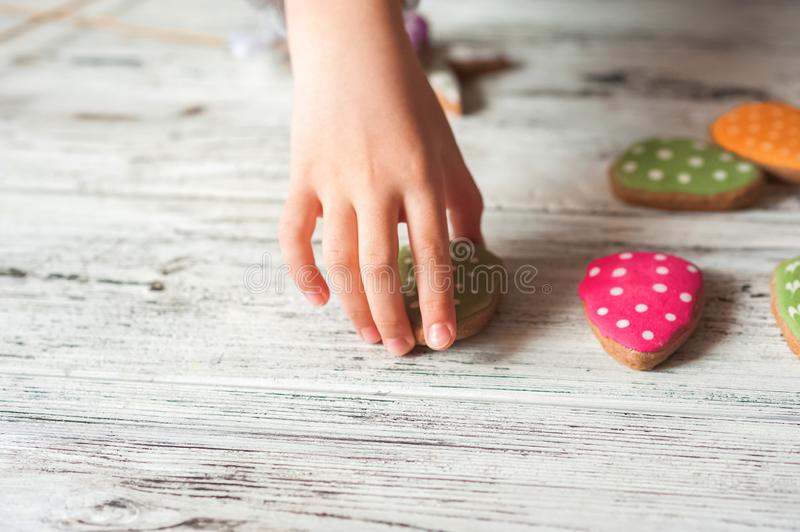 Painted ginger Easter gingerbread, colorful eggs and children`s hands on a wooden textured white background close-up and copy spac. E. Easter greeting card stock image