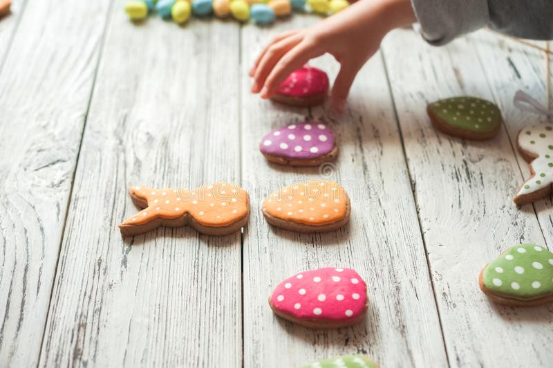Painted ginger Easter gingerbread, colorful eggs and children`s hands on a wooden textured white background close-up and copy spac. E. Easter greeting card stock photo