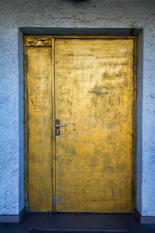 Painted in gold door with a blue white wall royalty free stock photos