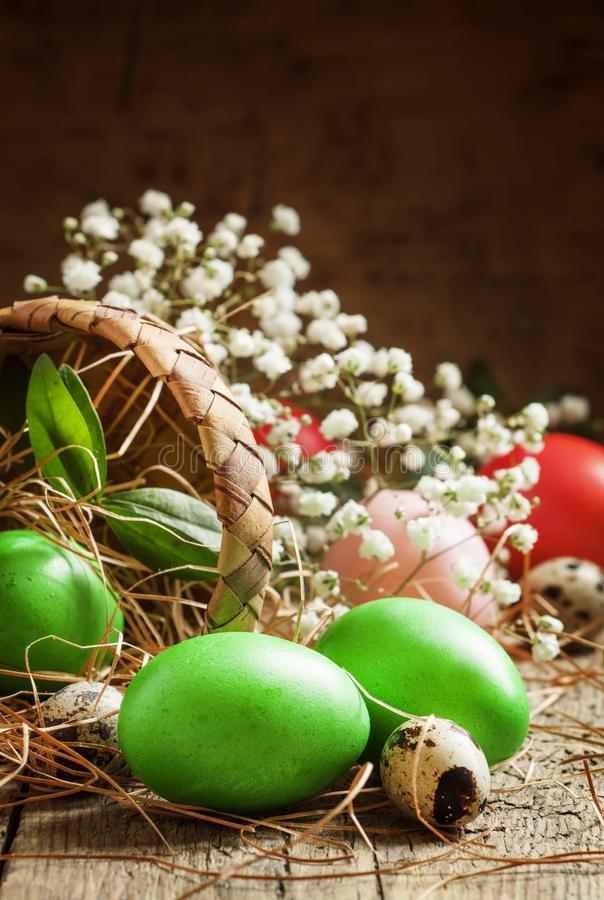 Painted green Easter eggs poured woven birch bark baskets in straw on the old wooden table in rustic style, selective focus stock image
