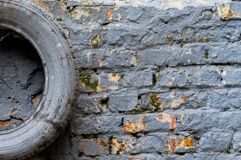 Painted in grey tyre lies on the gray brick wall stock photos