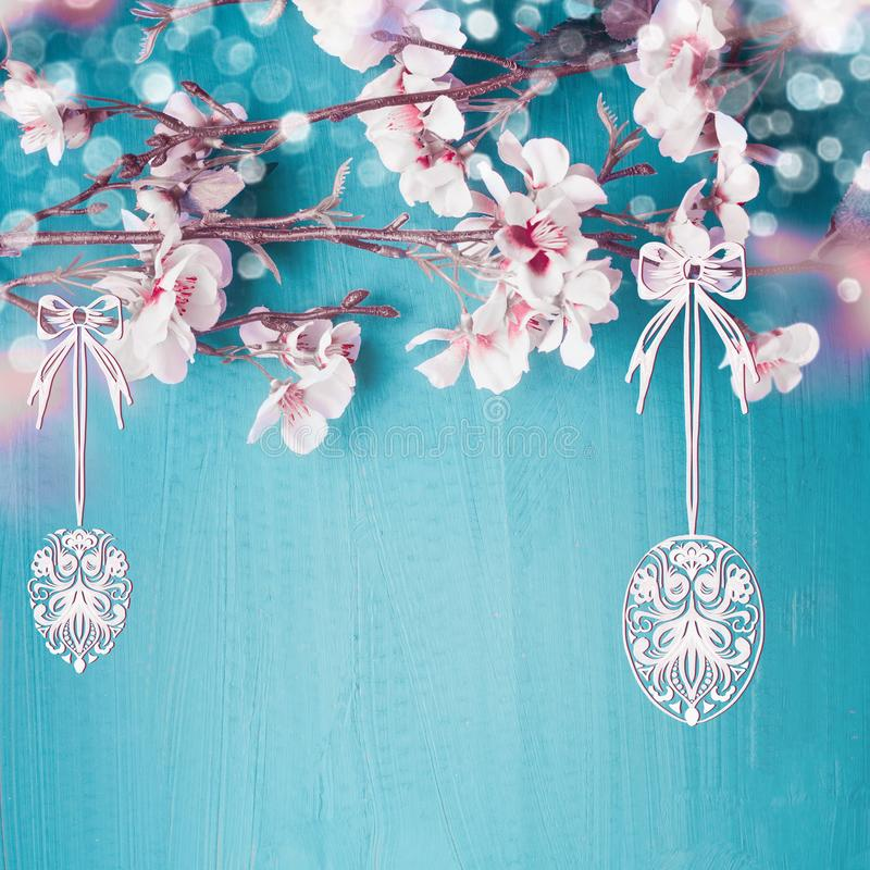 Painted hanging Easter eggs on spring cherry blossom branches at turquoise blue background. Easter greeting card stock images
