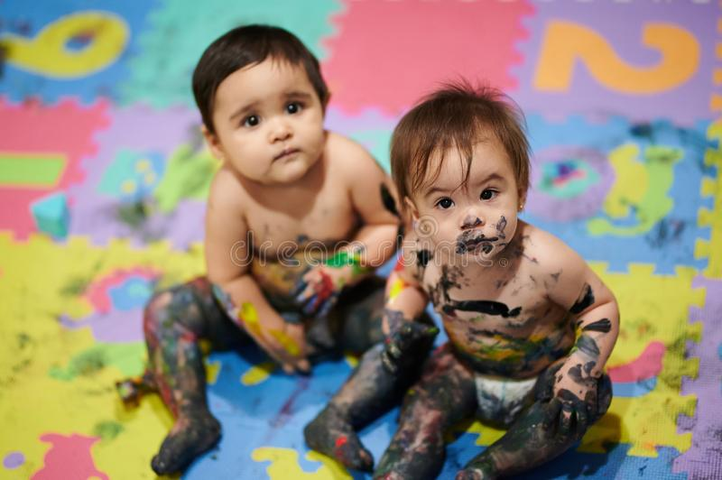 Painted kids bodies. Painted kids sitting on colorful background. Babies making mess royalty free stock photo