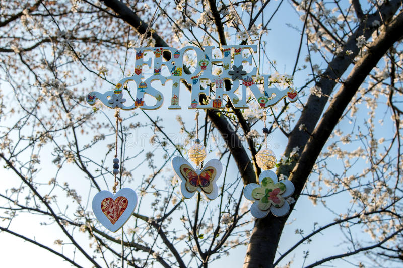 Painted letters Happy Easter in German on flowering tree. Decor for home and garden. Decorated painted congratulation Happy Easter in German. Letters are hanging stock photography