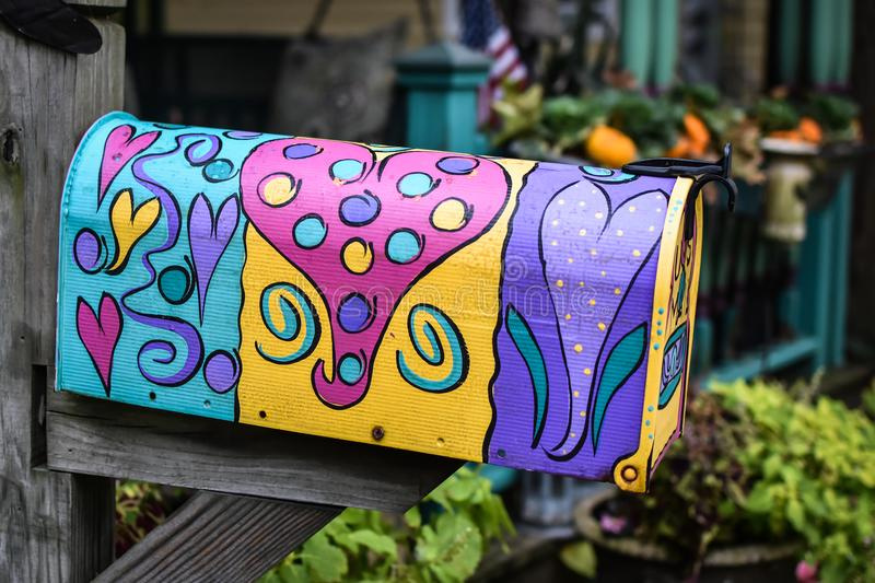 Painted Mailbox with Ultra Violet Hearts. A painted mailbox with hearts in pink, purple, teal, ultra violet, yellow and polka dots royalty free stock photos