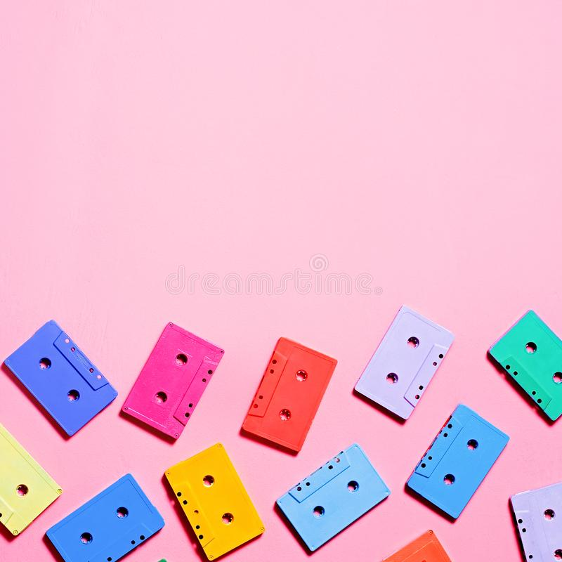 Painted multicolor audio cassettes on pink background, copy space, top view. Retro musical background stock photo