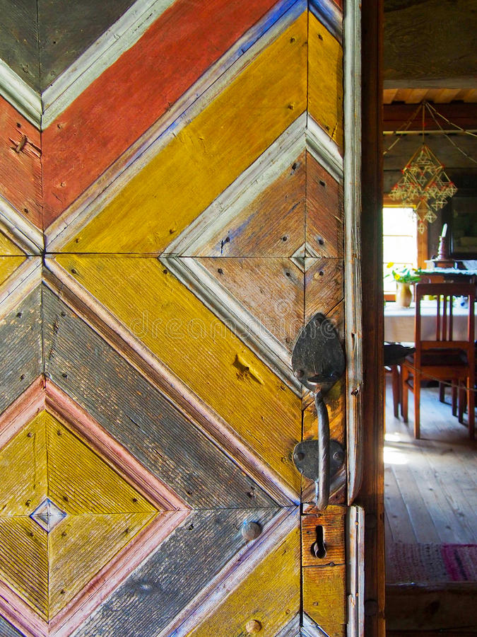 Painted Pattern on Rustic Wooden Door. A painted rustic wooden door with a colorful pattern opening into a rural home stock photography