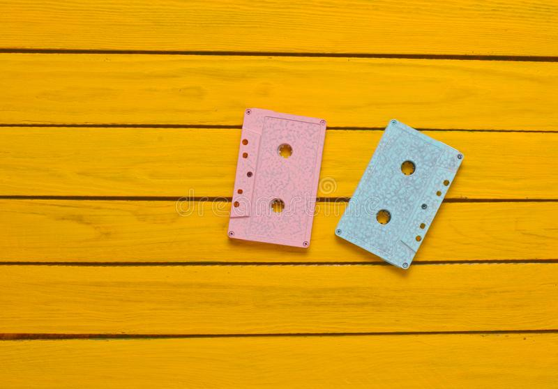 Painted in a pink blue pastel color audio cassette on a yellow wooden background. Retro audio technology royalty free stock photography