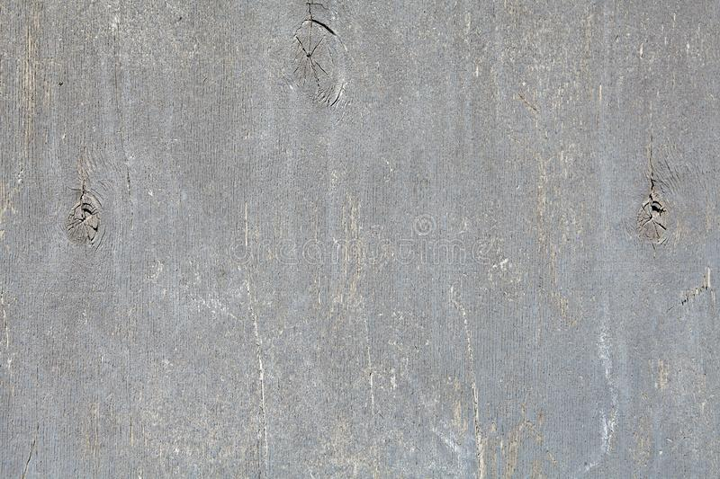 Painted plywood sheet with peeling gray paint. stock photo