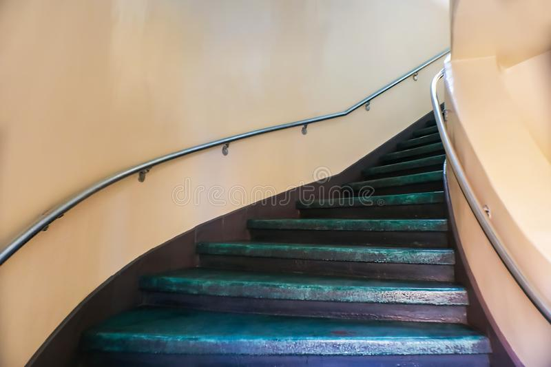 Painted purple curving concrete stairs with stuco walls disappearing around the curve royalty free stock images