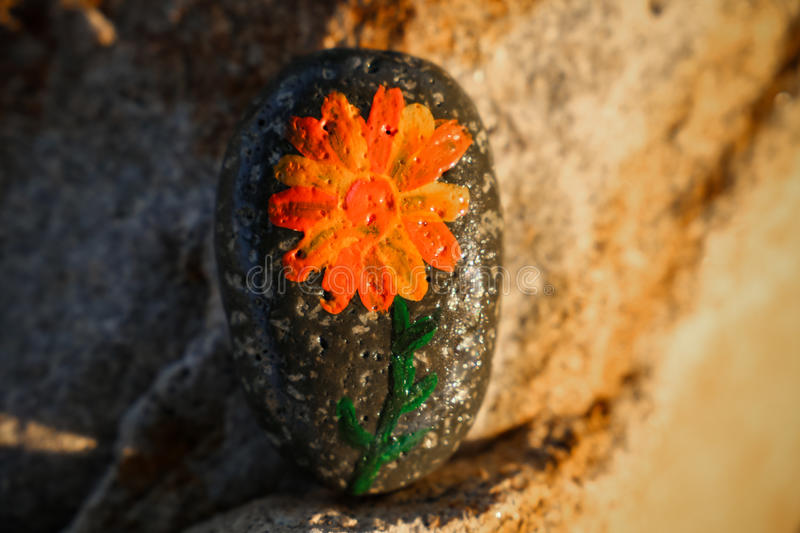 Painted rock with a flower stock photos