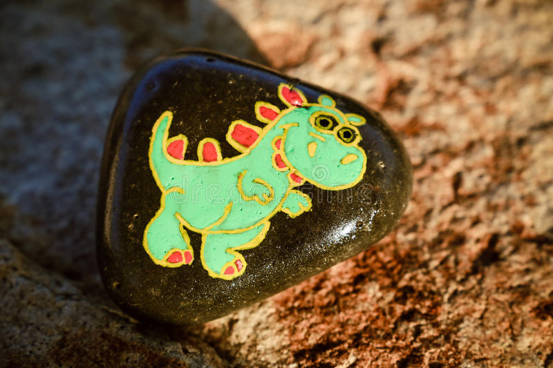 Painted rock with a green dinosaur. A rock is painted black with a cute, smiling green dinosaur. Stone is for a child or yard art or garden art and is sitting royalty free stock image