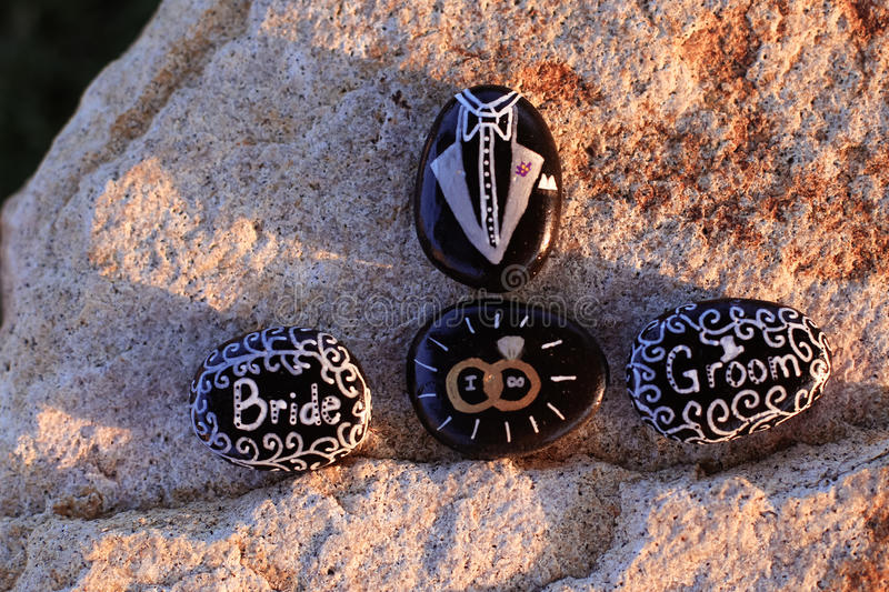 Painted rocks stating Bride, Groom, `I DO,` and a tux stock photos