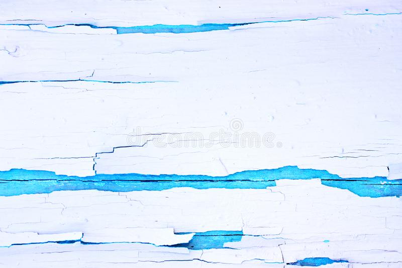 Painted rough wooden background, old wall with cracked paint white on blue backdrop. stock image