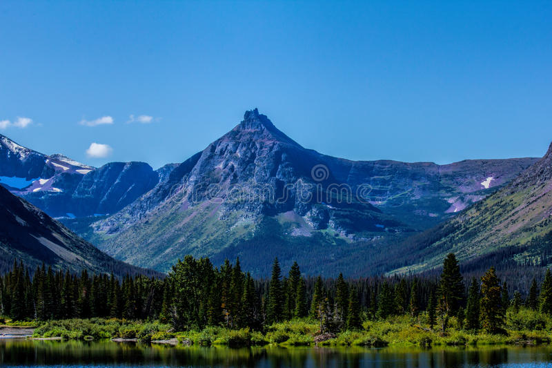Painted Teepee Mountain. This image shows Painted Teepee Mountain and a portion of Pray Lake in Glacier National Park, MT royalty free stock photo