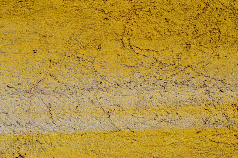 Painted textured wall. Coarse cracked plastered wall airbrushed with yellow graffiti paint stock photos