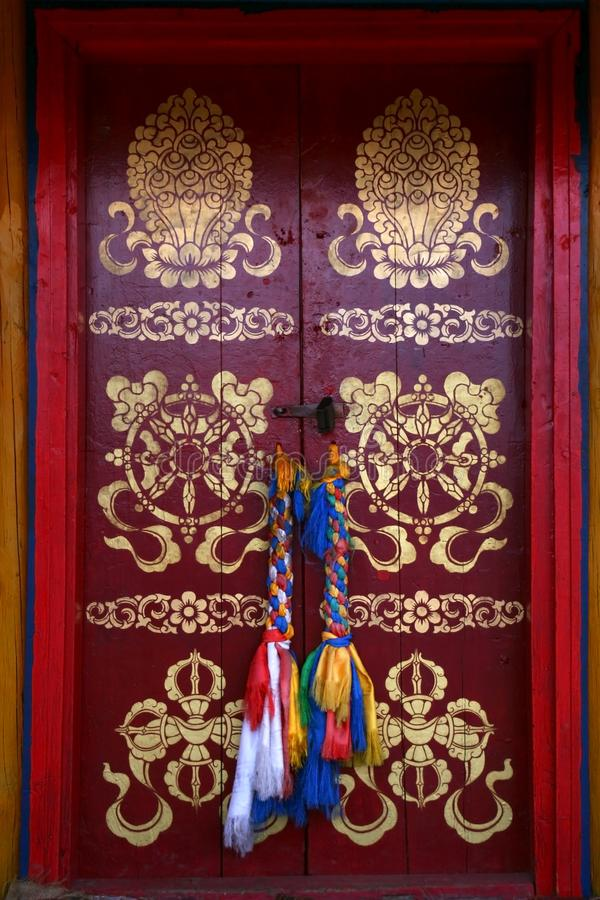 Painted with traditional buddhist symbols red door with laced hadags sacred scarves as handles in Tovkhon Monastery, Mongolia royalty free stock photo