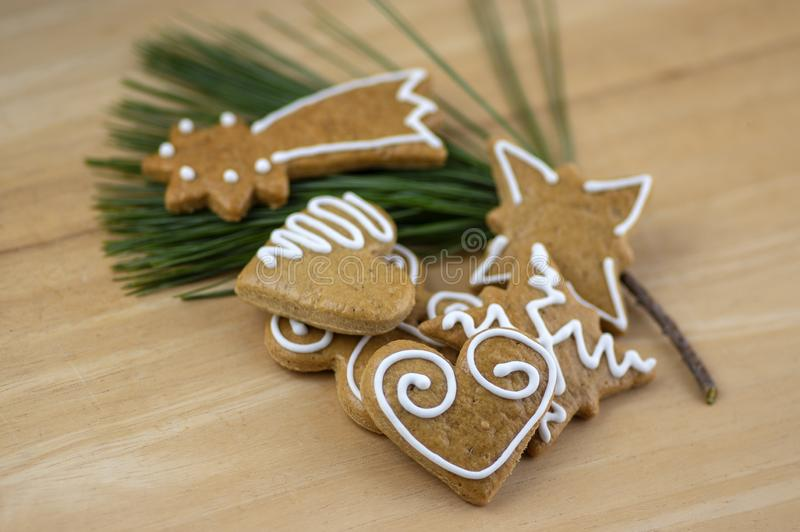 Painted traditional Christmas gingerbreads arranged on wooden background in daylight, common tasty sweets on pine branch needles stock photos