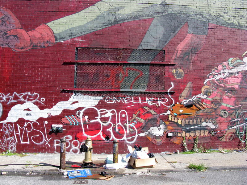Painted wall on Brooklyn street. A brick wall in on a street in Brooklyn, New York is painted with images, designs and graffiti royalty free stock photos