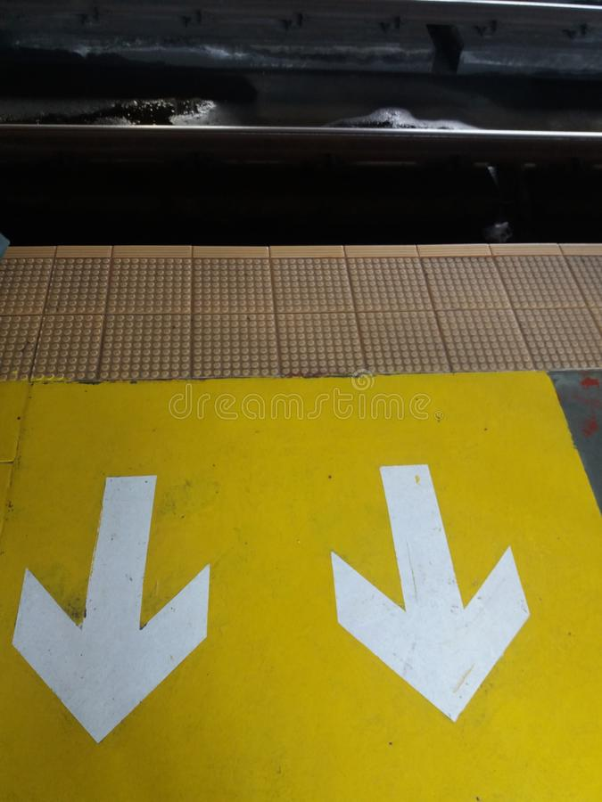 Painted white arrows on a yellow box sign with train rails. And cream colored stepping tiles at Manila, Philippines stock photos