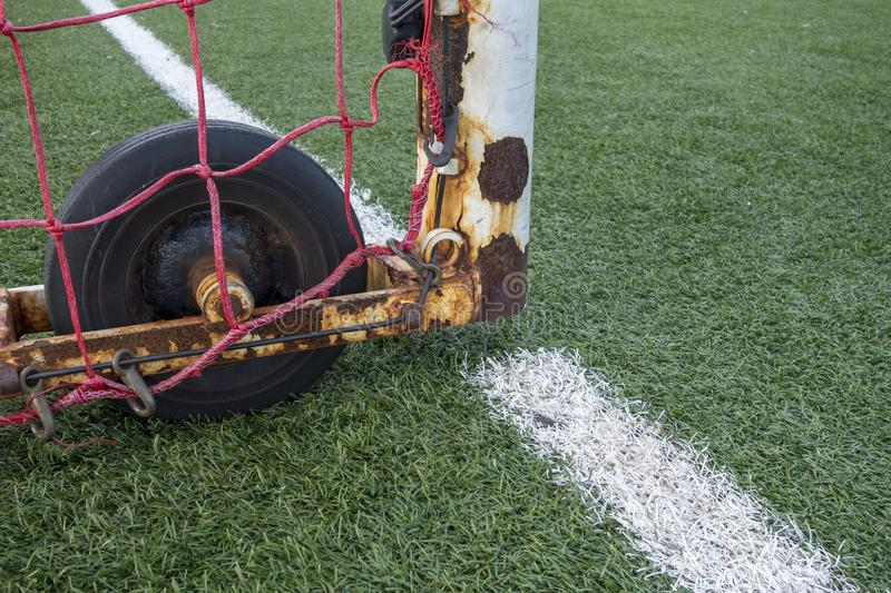 Close up of white goalie cage, rubber wheel,artificial Green lawn soccer European football astroturf with white field markings and stock photography