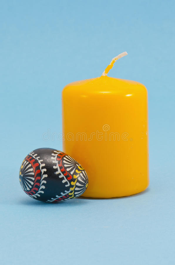 Painted wooden easter egg and yellow candle